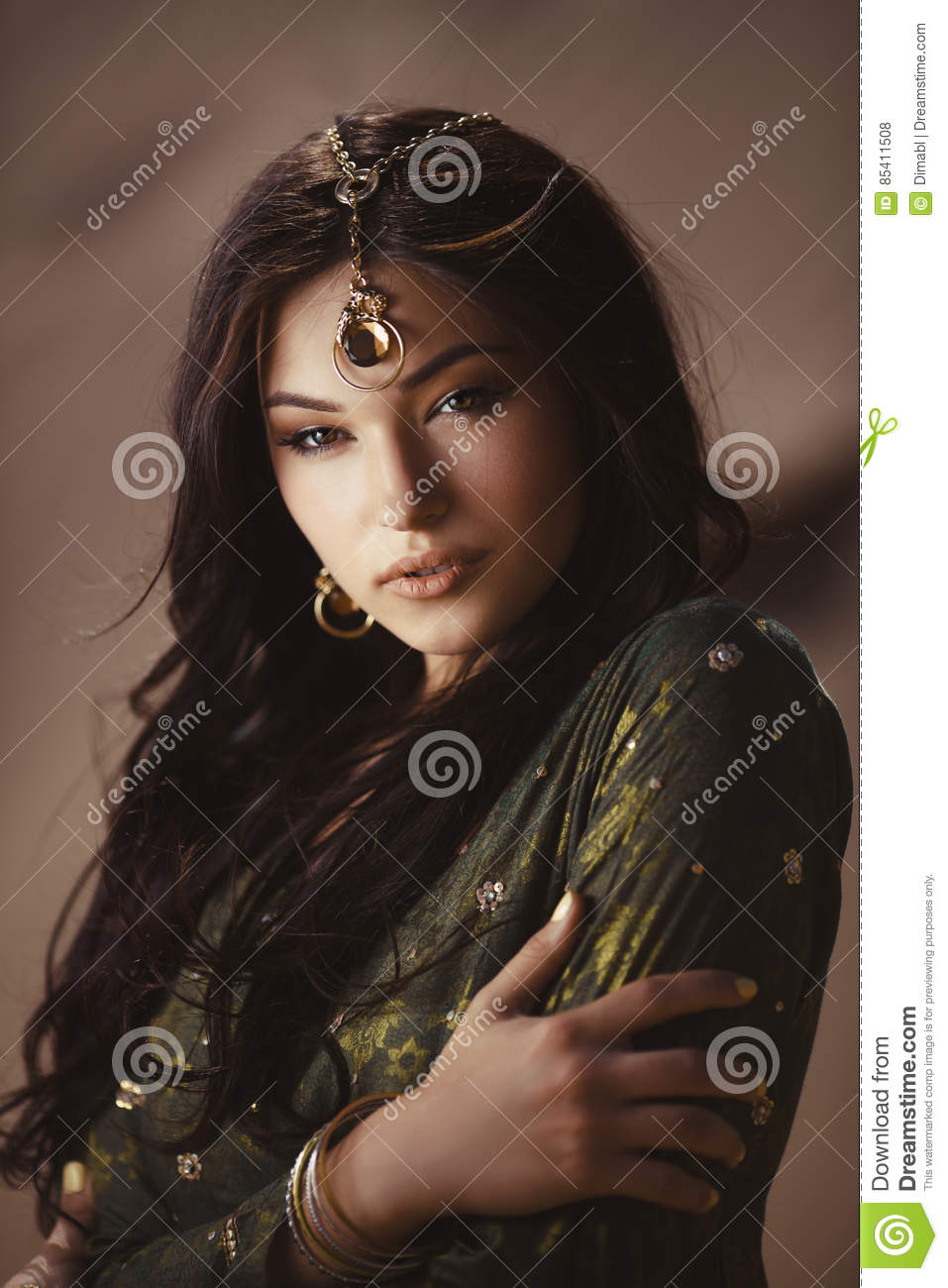 Beautiful woman with fashion make-up and hairstyle like Egyptian princess Cleopatra outdoors against desert