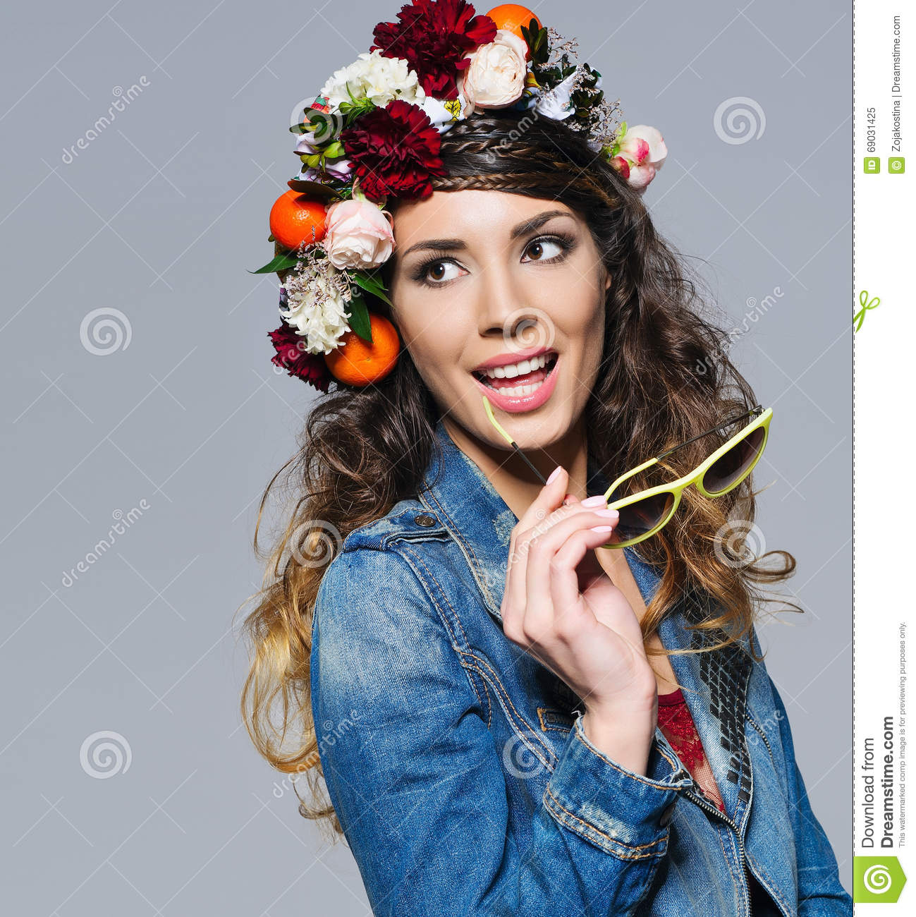 Beautiful woman in flower crown holding sunglasses stock image fashion portrait of a beautiful young woman with gipsy hairstyle wearing bright flower crown jeans jacket and trendy yellow sunglasses smiling happily izmirmasajfo