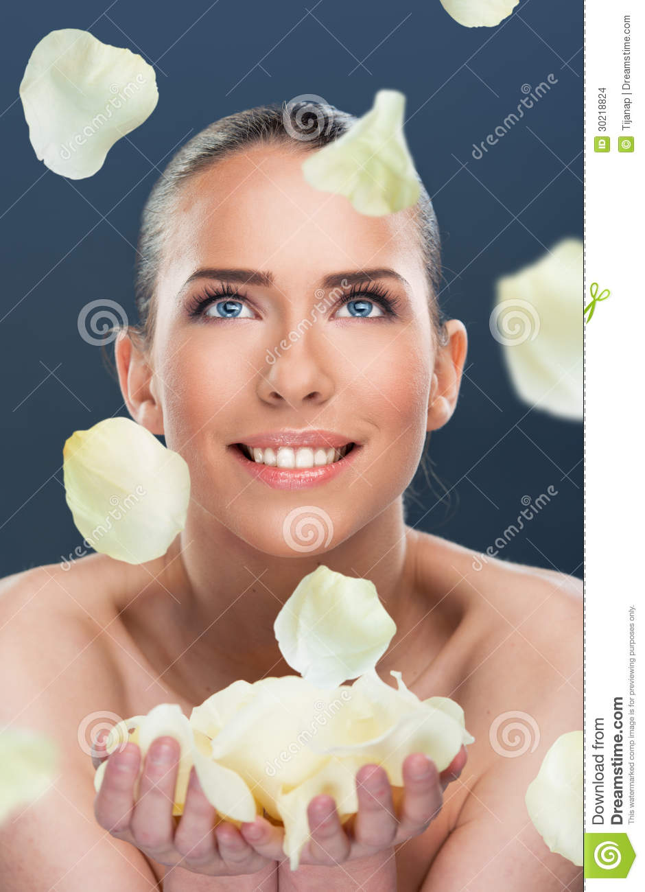 Beautiful woman with flower petals falling, close up