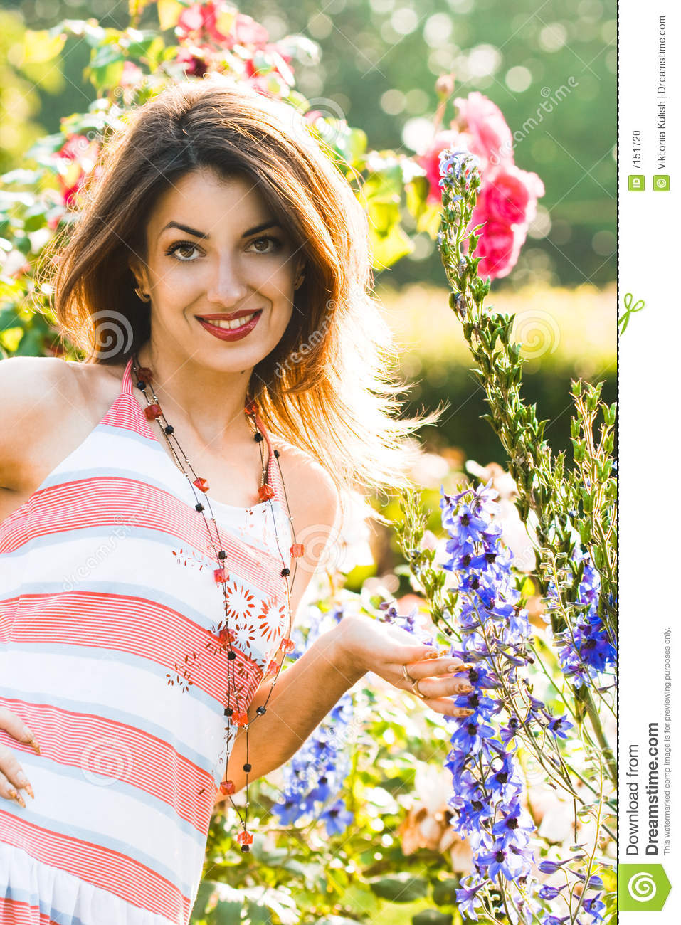 Beautiful girl in spring garden among the blooming trees