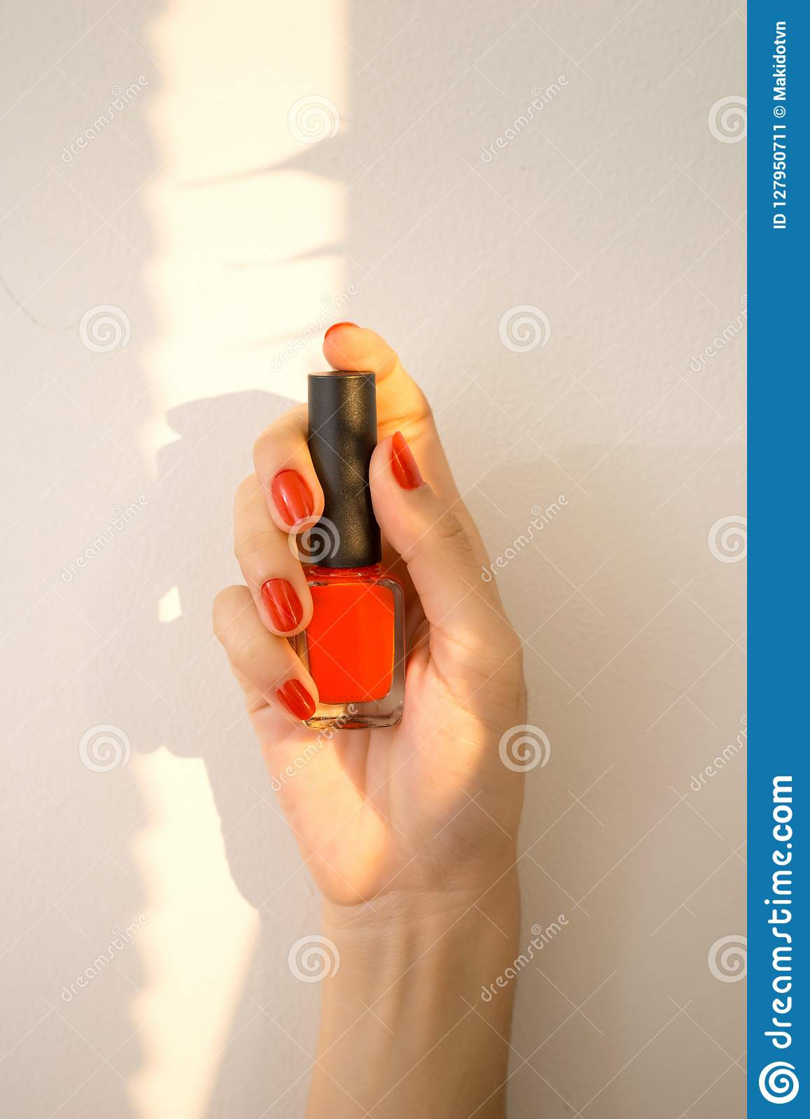 Beautiful Woman Hand With Red Manicure Holding Nail Polish