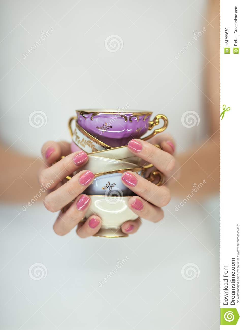 Beautiful woman hands with perfect pink nail polish holding little vintage tea cups