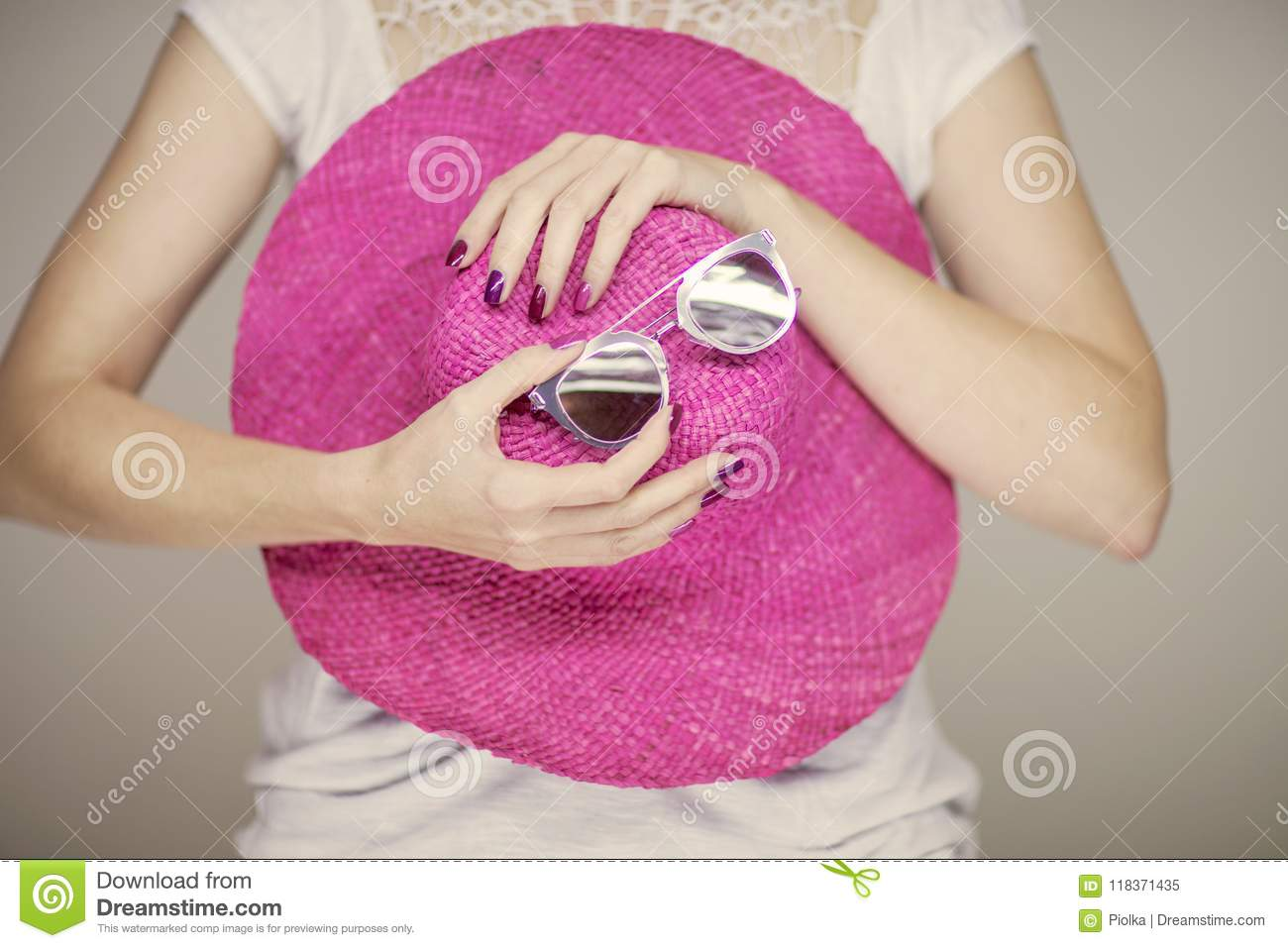 Beautiful woman hands with perfect pink nail polish holding sunhat and sunglasses, happy beach mood
