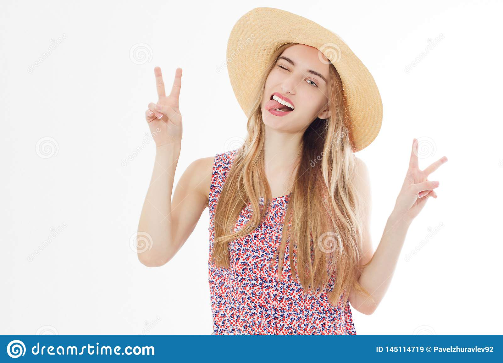 Beautiful woman with hat smiling on a background of white show victory signs and tongue