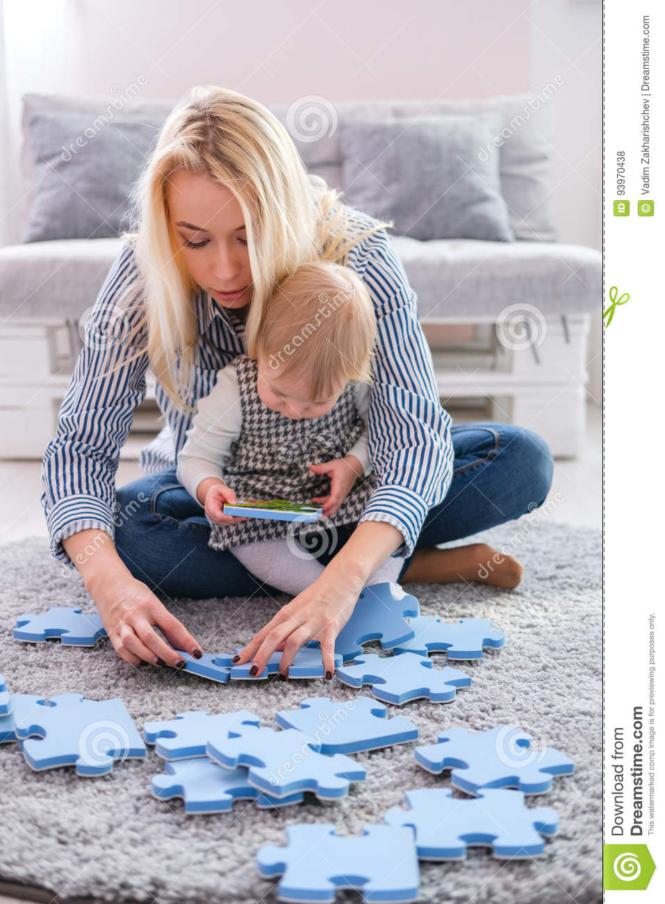 Beautiful Woman And Her Baby Playing With Puzzle Pieces While Sitting On A Carpet In The Living