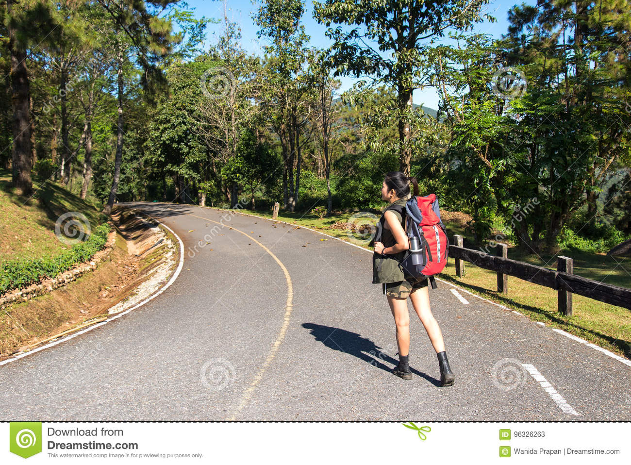 Beautiful woman hiker standing on forest trail and looking away. Female with backpack on hike in nature.
