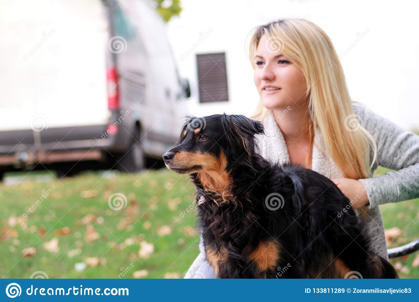 Beautiful woman with his small mixed breed dog sitting and posing in front of camera on wooden bench at city park.