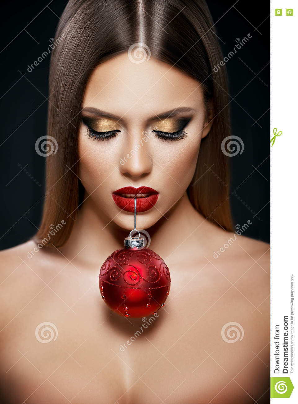 Beautiful woman holding a Christmas ornament with teeth over dark background