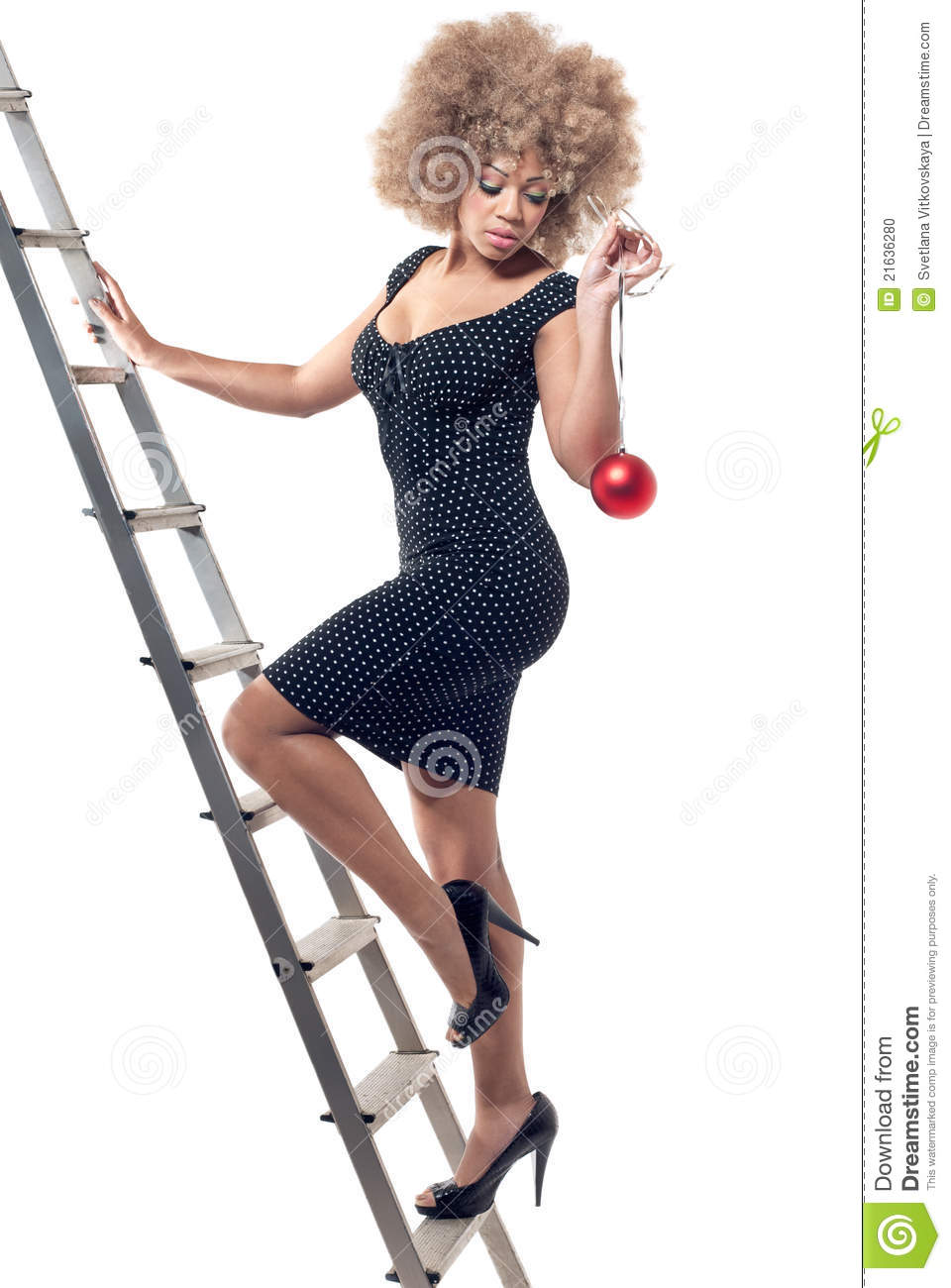 Beautiful Woman On Ladder Holding A Christmas Ball Stock