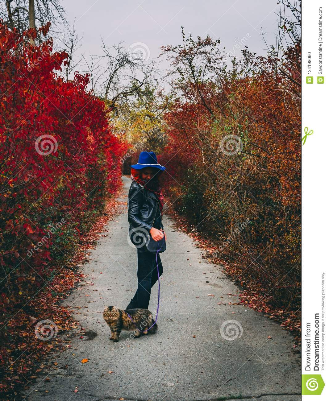Woman with cat walks at autumn park