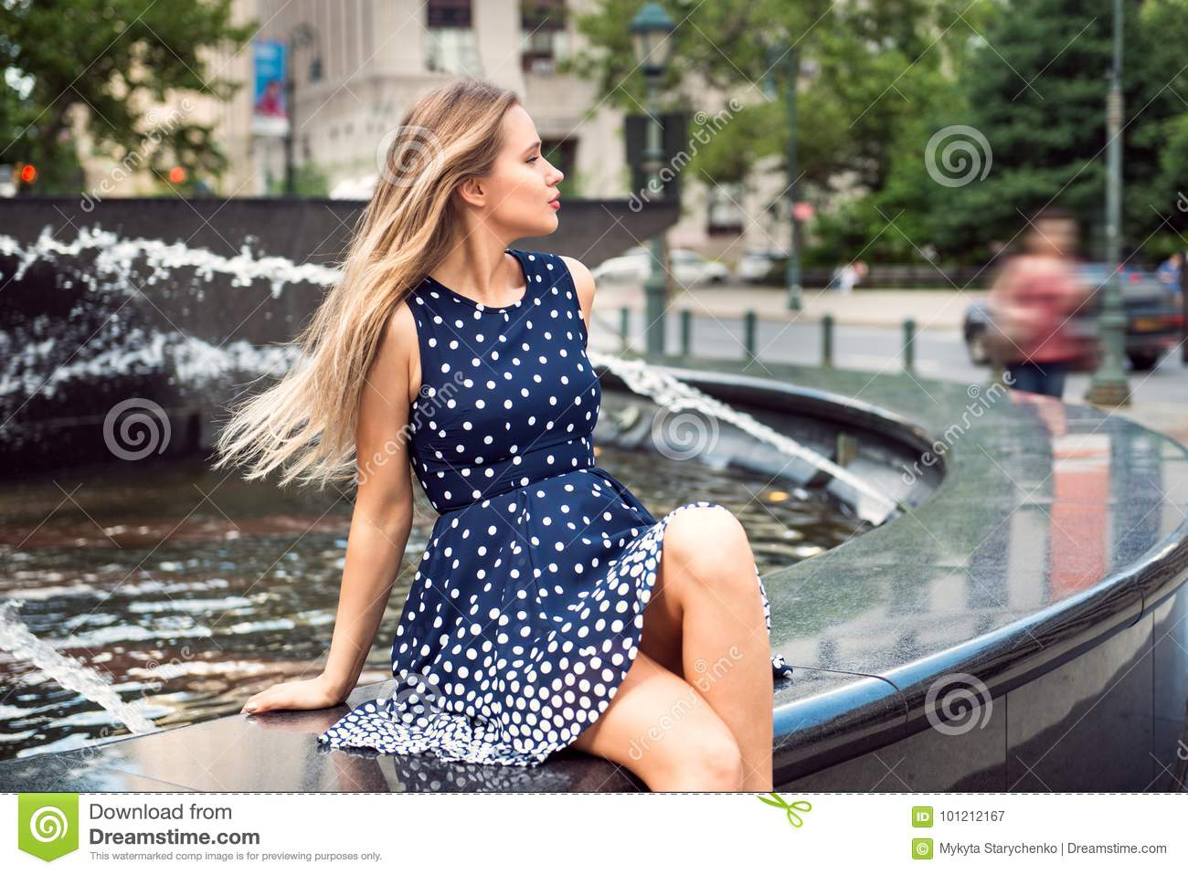 Beautiful woman with long blond hair sitting in the city park at summer time.