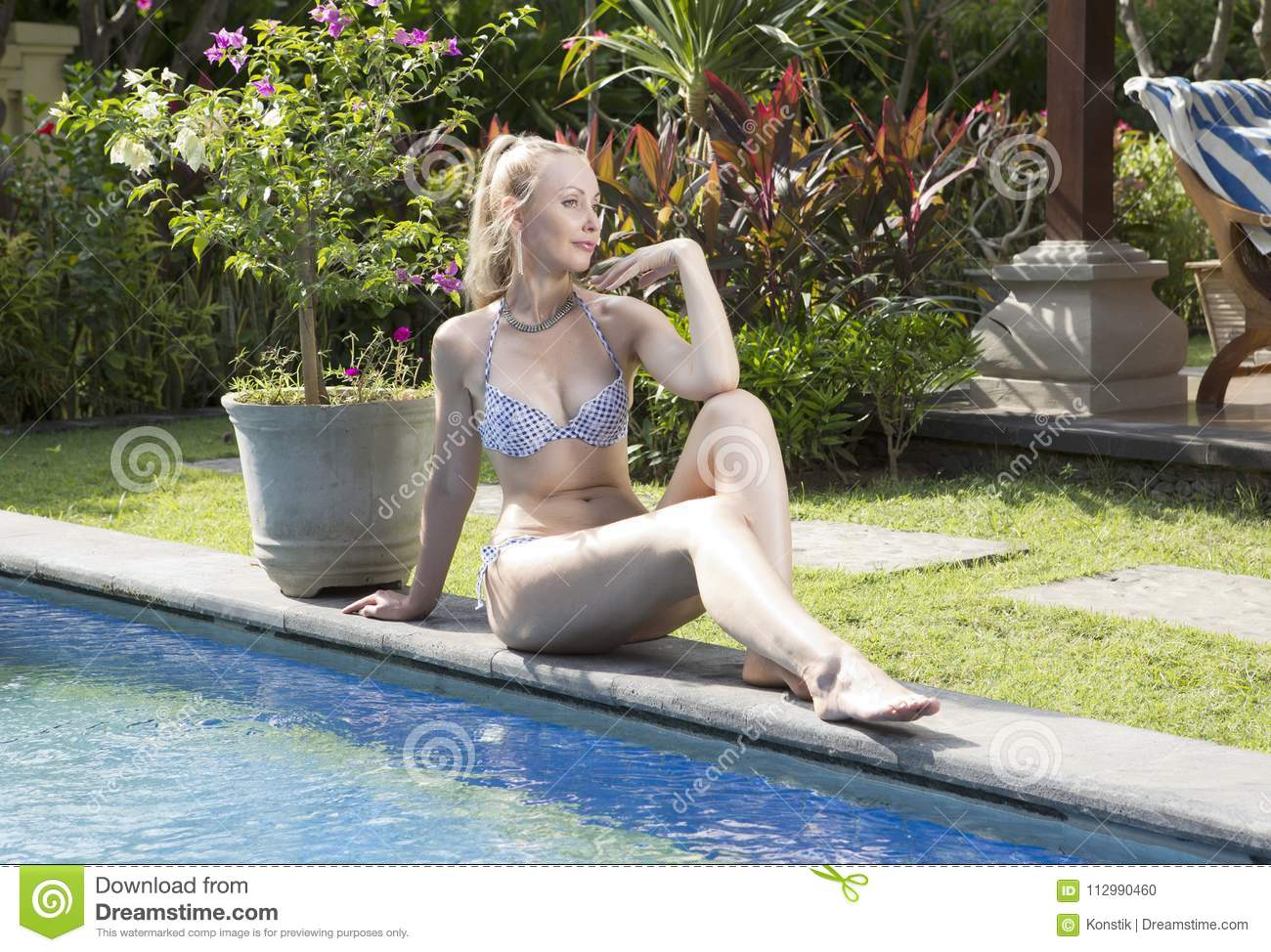 Beautiful woman with with a long blond hair, a slim figure in a bikini swimwear about the pool with bright blue water in a tropic