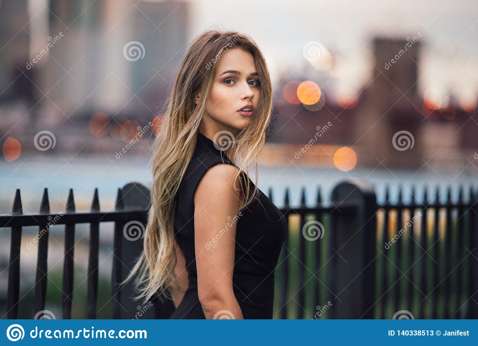 Beautiful woman with long blond hair walking in the city at evening time wearing elegant black dress.
