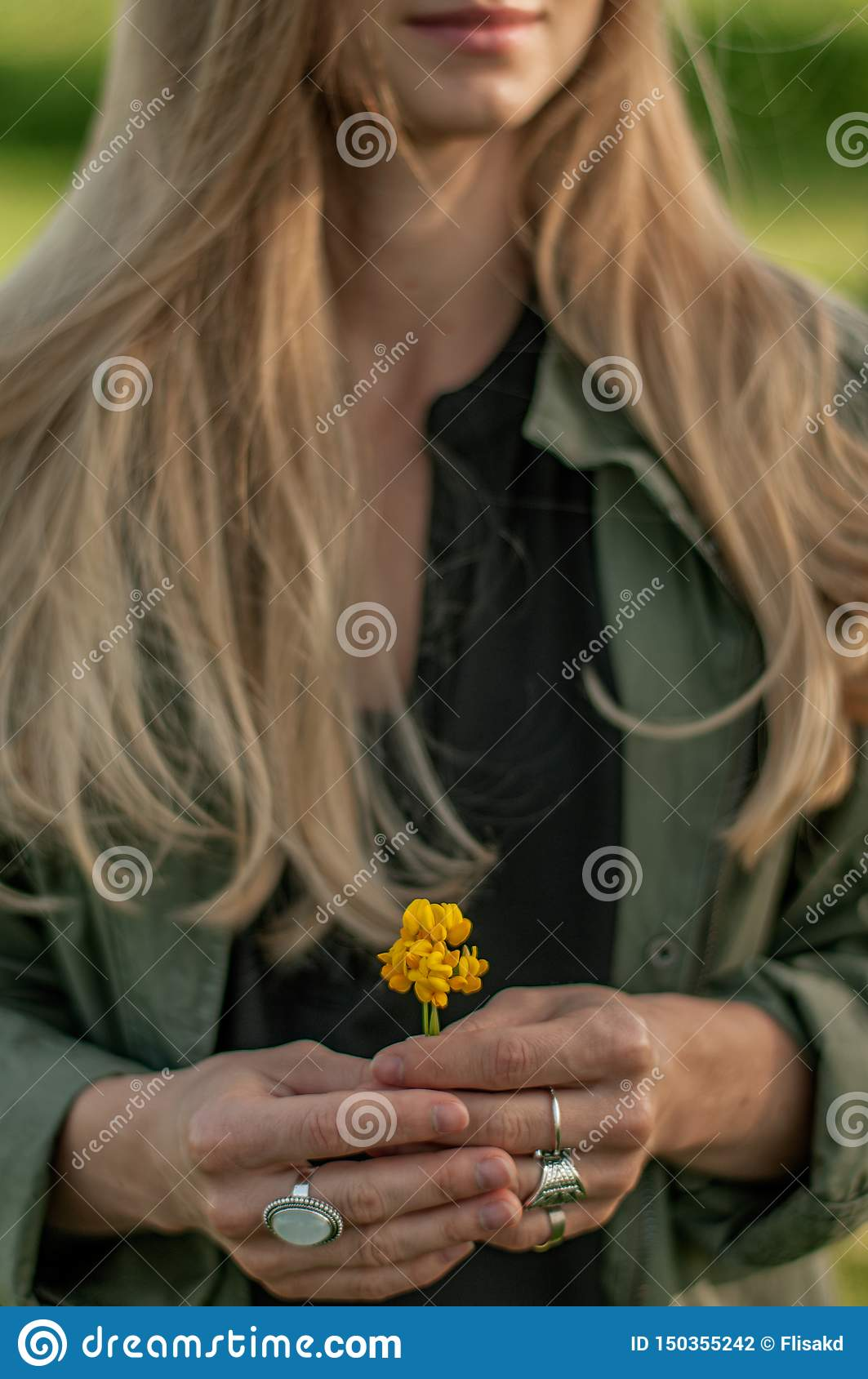 Beautiful woman with long hair holding flower. Hands with rings stylish boho accessories. No focus