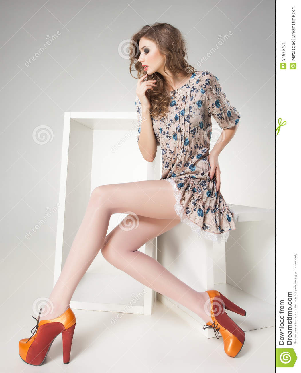 Beautiful woman with long legs in summer dress posing