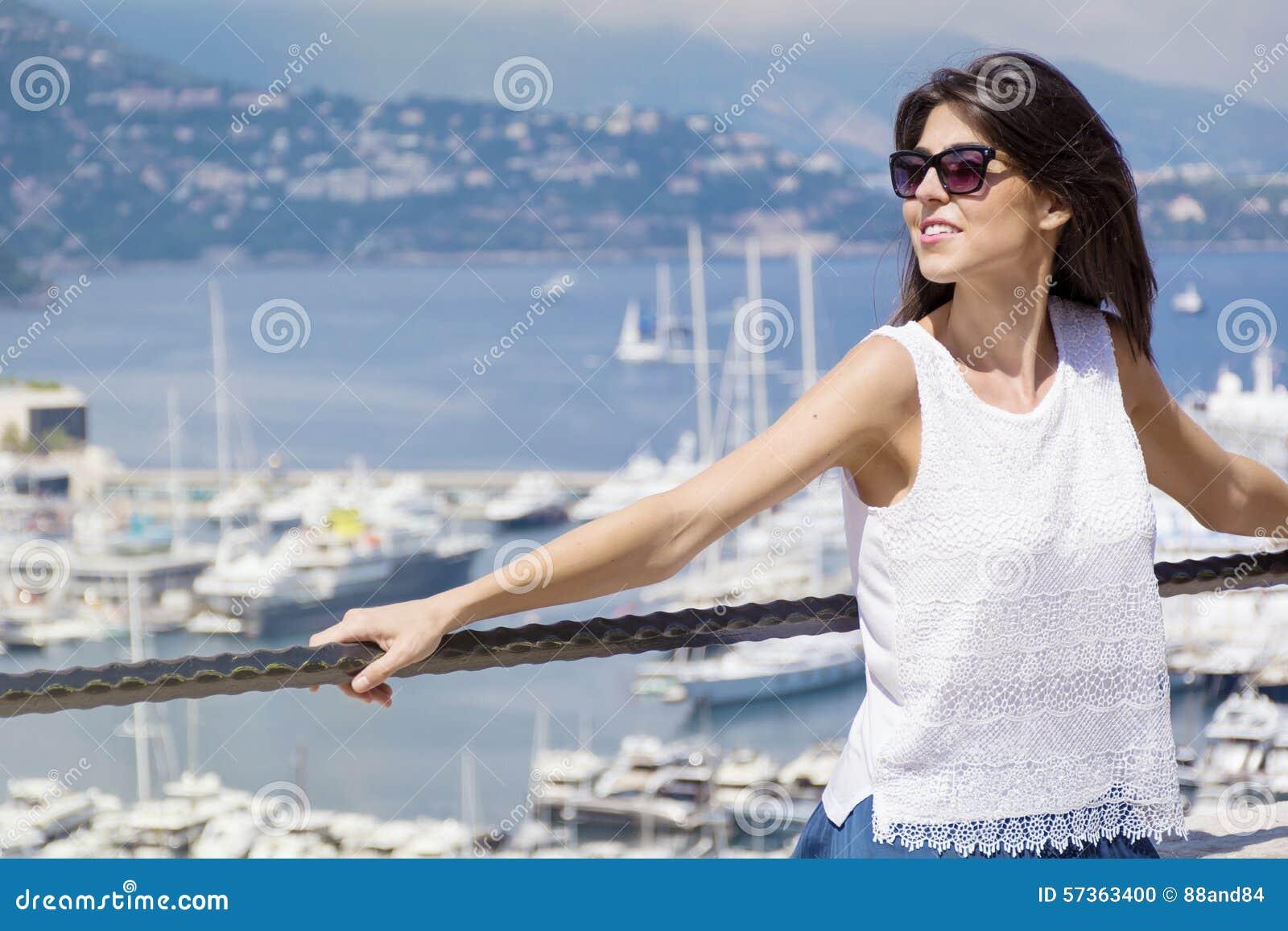 Beautiful woman looking at Monte Carlo harbour in Monaco. Azur coast.