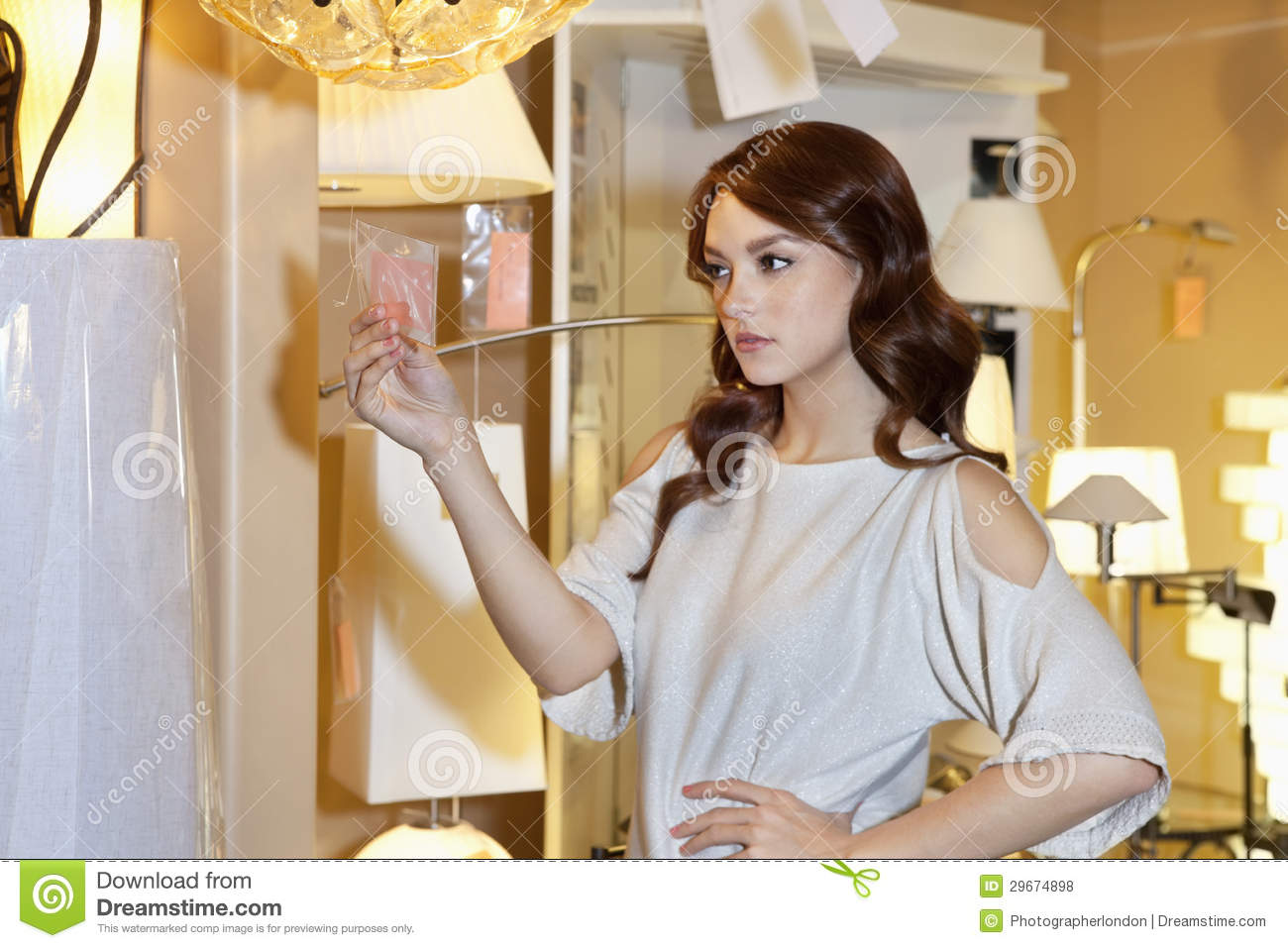 Beautiful Woman Looking At Price Tag Of Lighting Fixture