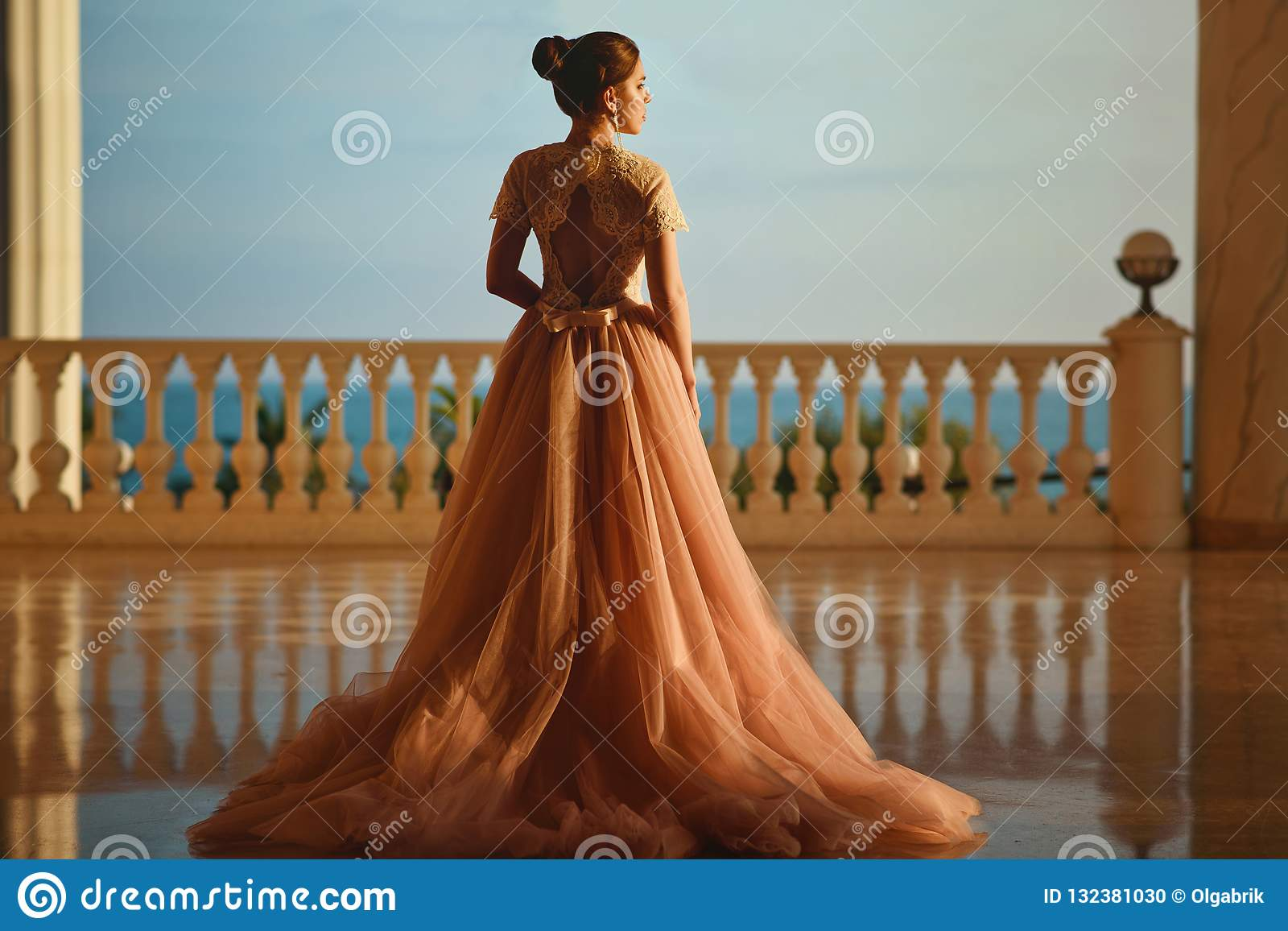 Beautiful woman in luxurious ballroom dress with tulle skirt and lacy top standing on the large balcony with sea view