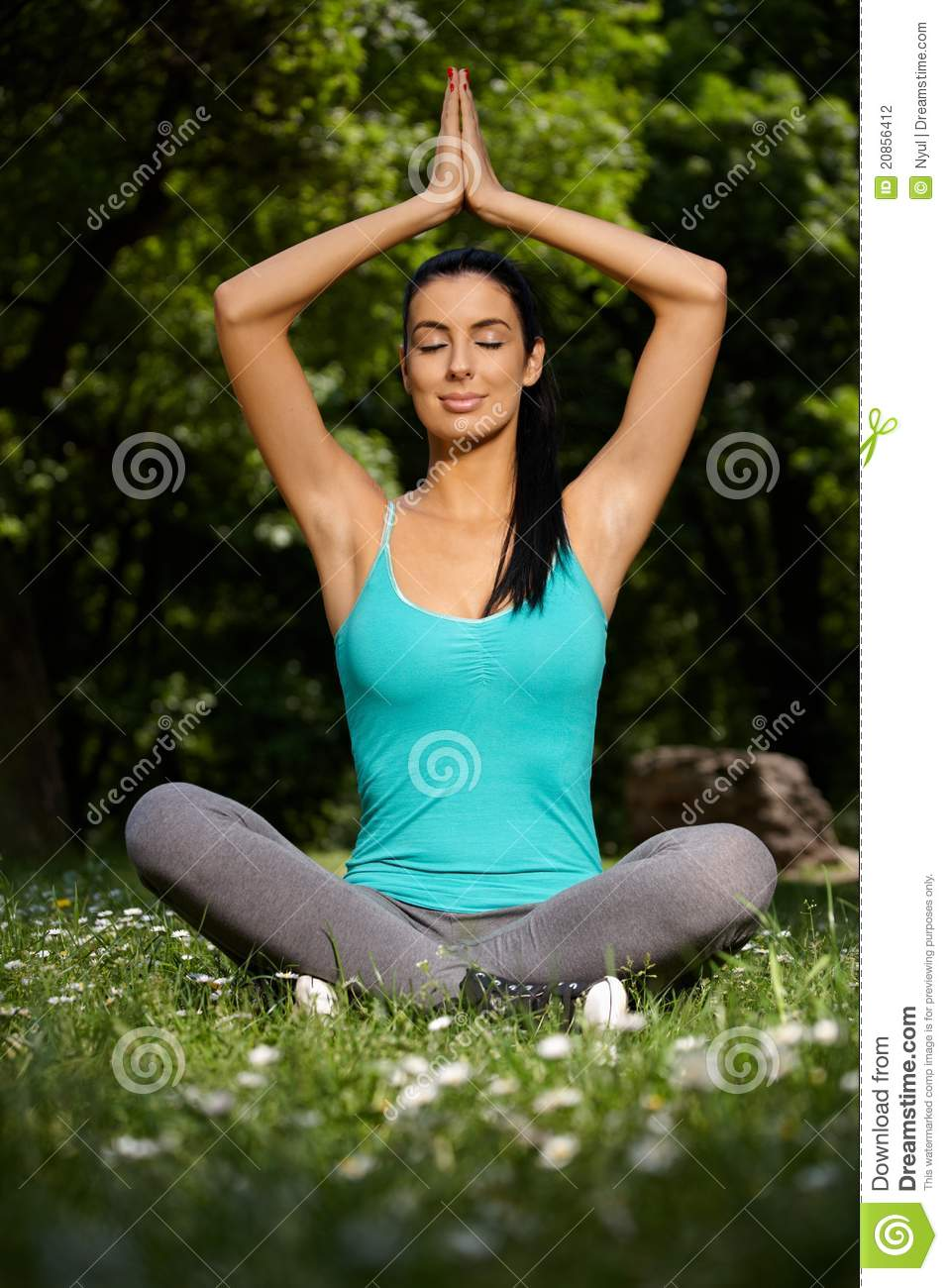 Beautiful woman meditating in yoga pose in park