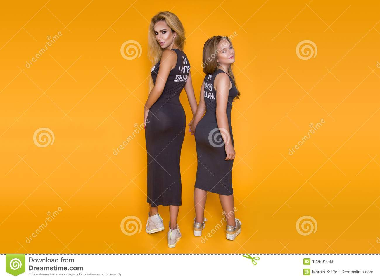 Beautiful, woman, mother with daughter, dressed in the same summer dresses, posing on a yellow background.