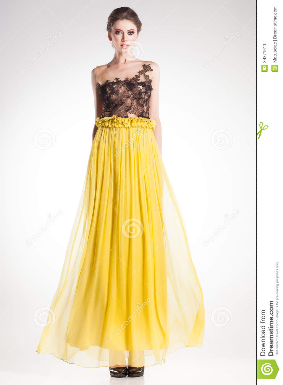 Beautiful woman model posing in long yellow dress with black lace
