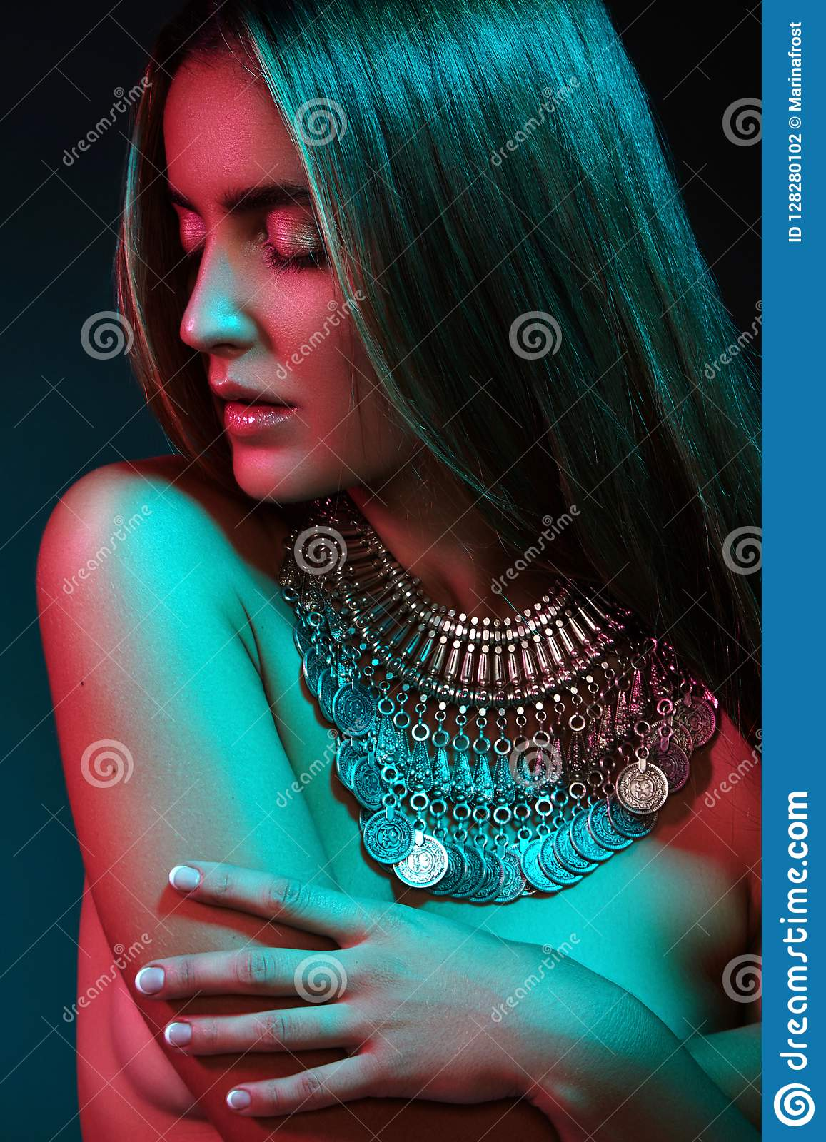 Beautiful woman in a necklace. Model in jewelry from silver. Beautiful indian jewellery. Bright lights
