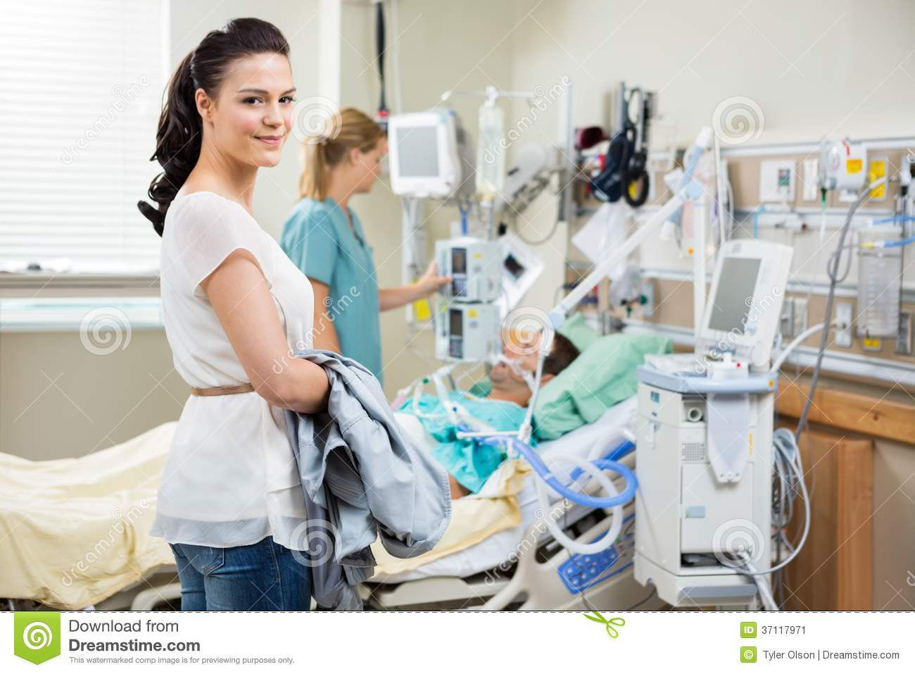 beautiful young women with nurse examining male patient in hospital