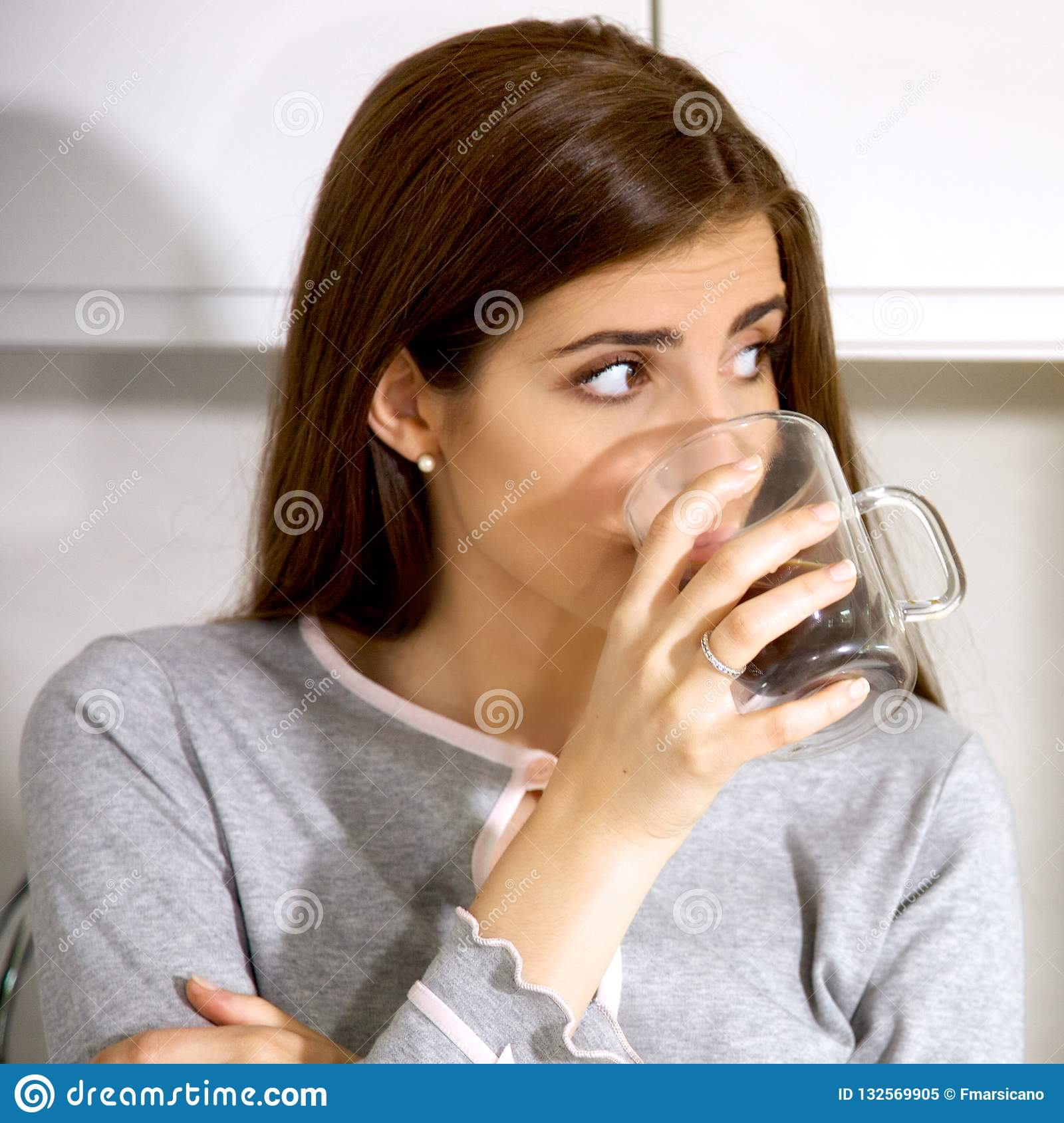 da04481876c8 Beautiful woman in pajamas in the morning holding drinking coffee at home  closeup