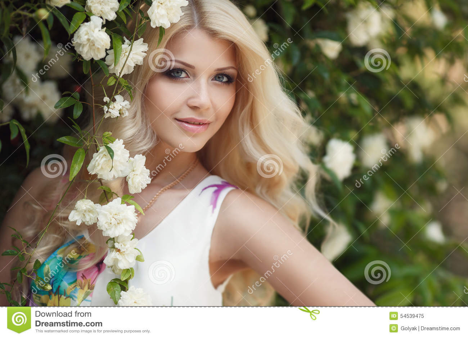 Women Blonde Blue Eyes Long Hair Wavy Hair Portrait: Beautiful Woman In Park Near The Bush Blooming Roses Stock