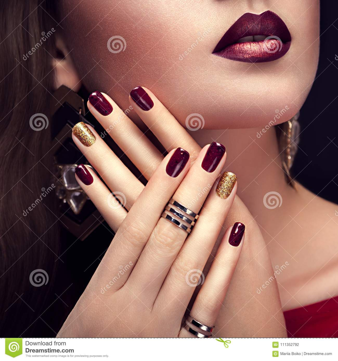 Beautiful woman with perfect make-up and burgundy and golden manicure wearing jewellery