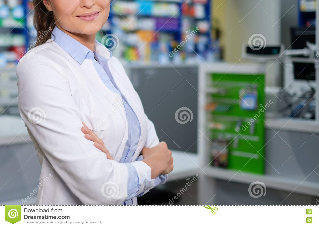 Beautiful woman pharmacist standing at her workplace in pharmacy.