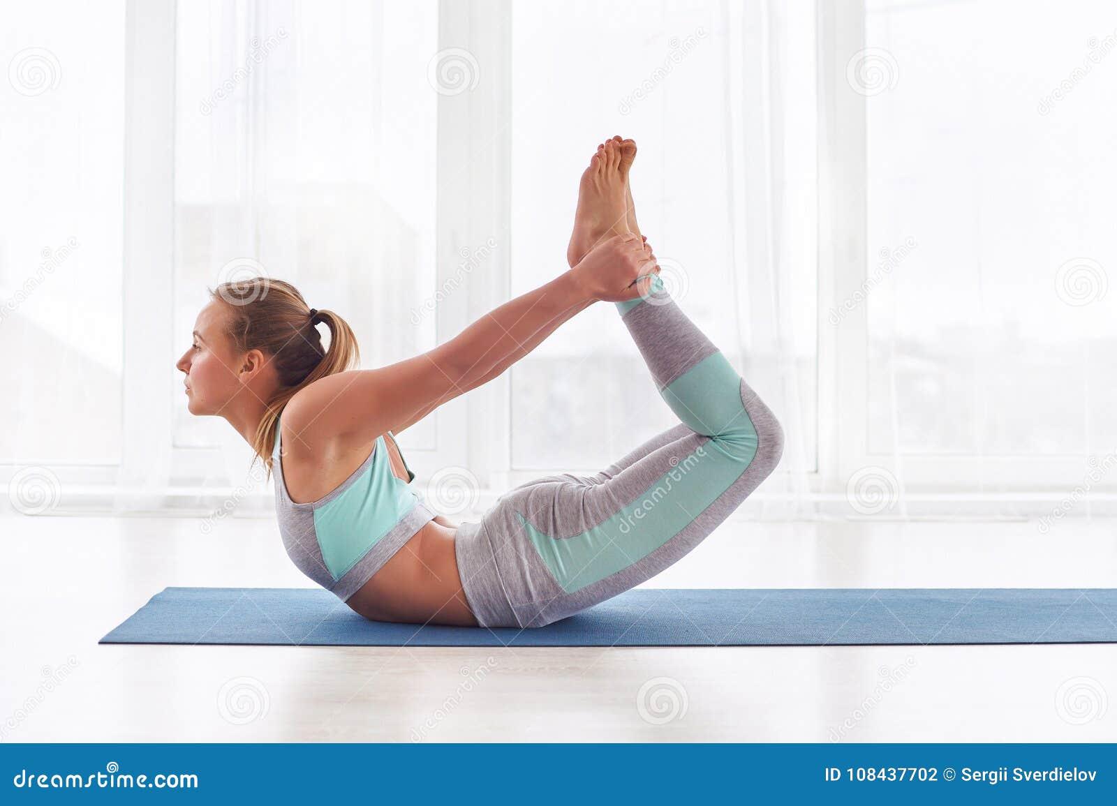 Beautiful Woman Practices Yoga Asana Dhanurasana - Bow Pose At The