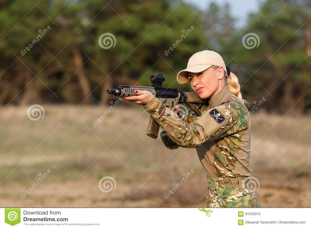 Beautiful woman ranger with rifle in camouflage