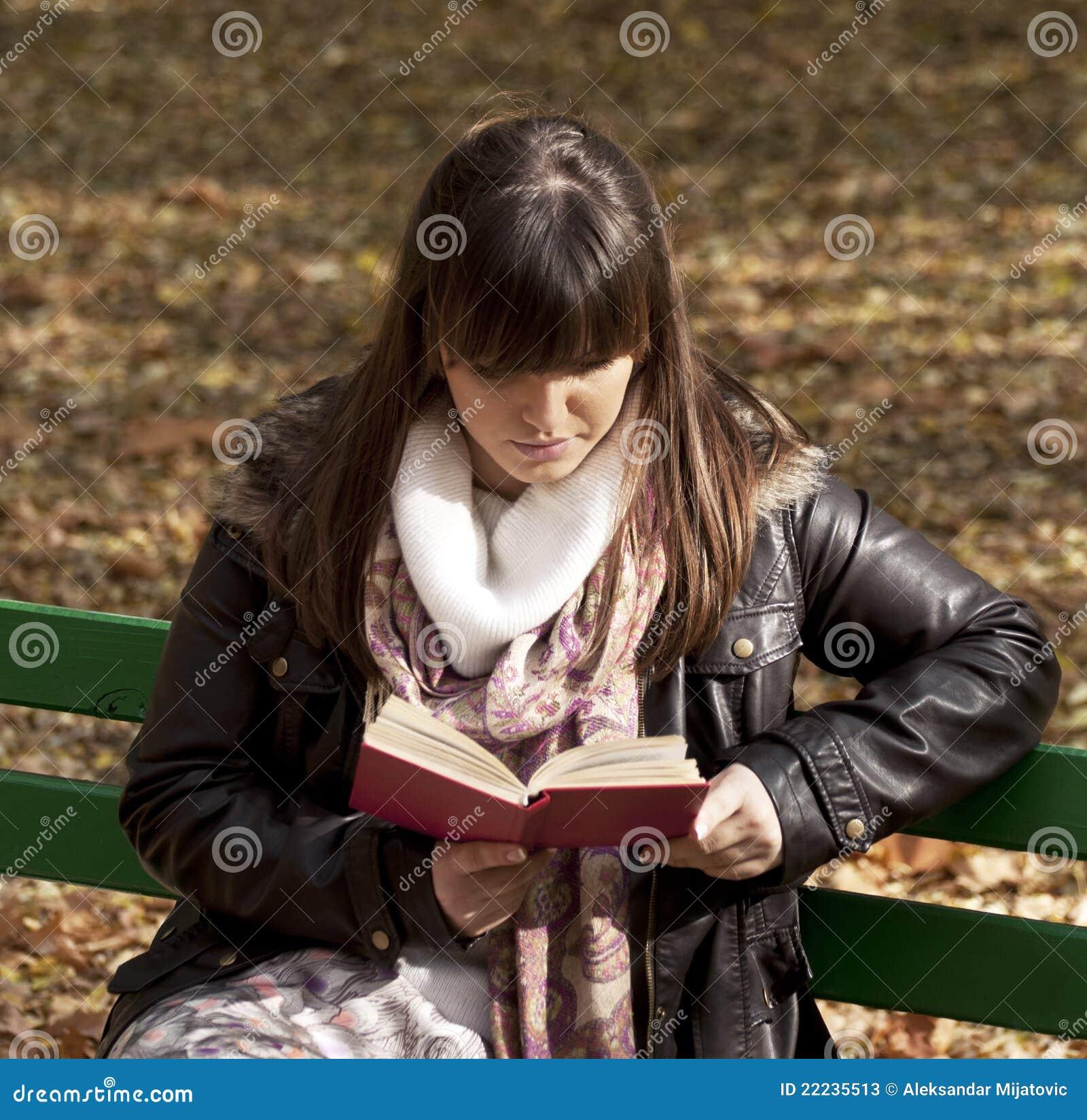 Beautiful woman reading book in park
