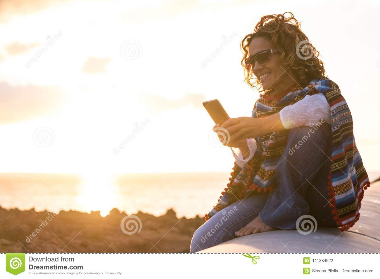 beautiful woman reading message on mobile phone in vacation during golden hour