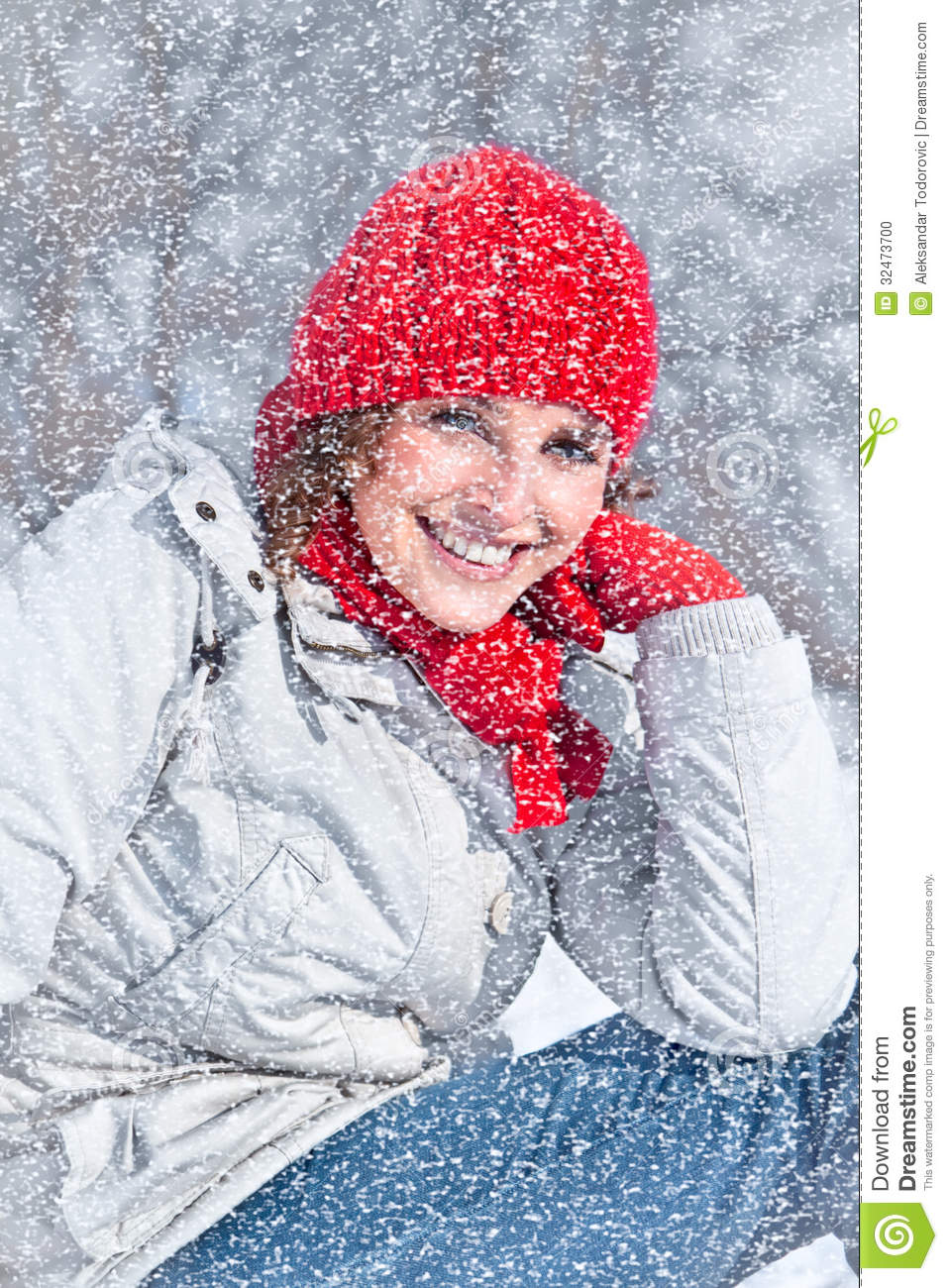 Beautiful woman with red cap on the snow day.