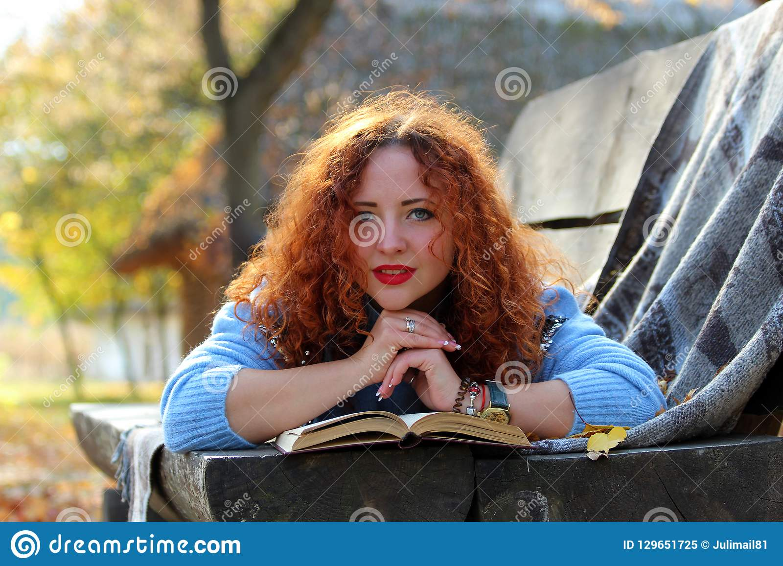 Beautiful woman with red hair is lying on a bench with a book and yellow leaves and looking into the camera. Autumn park backgroun
