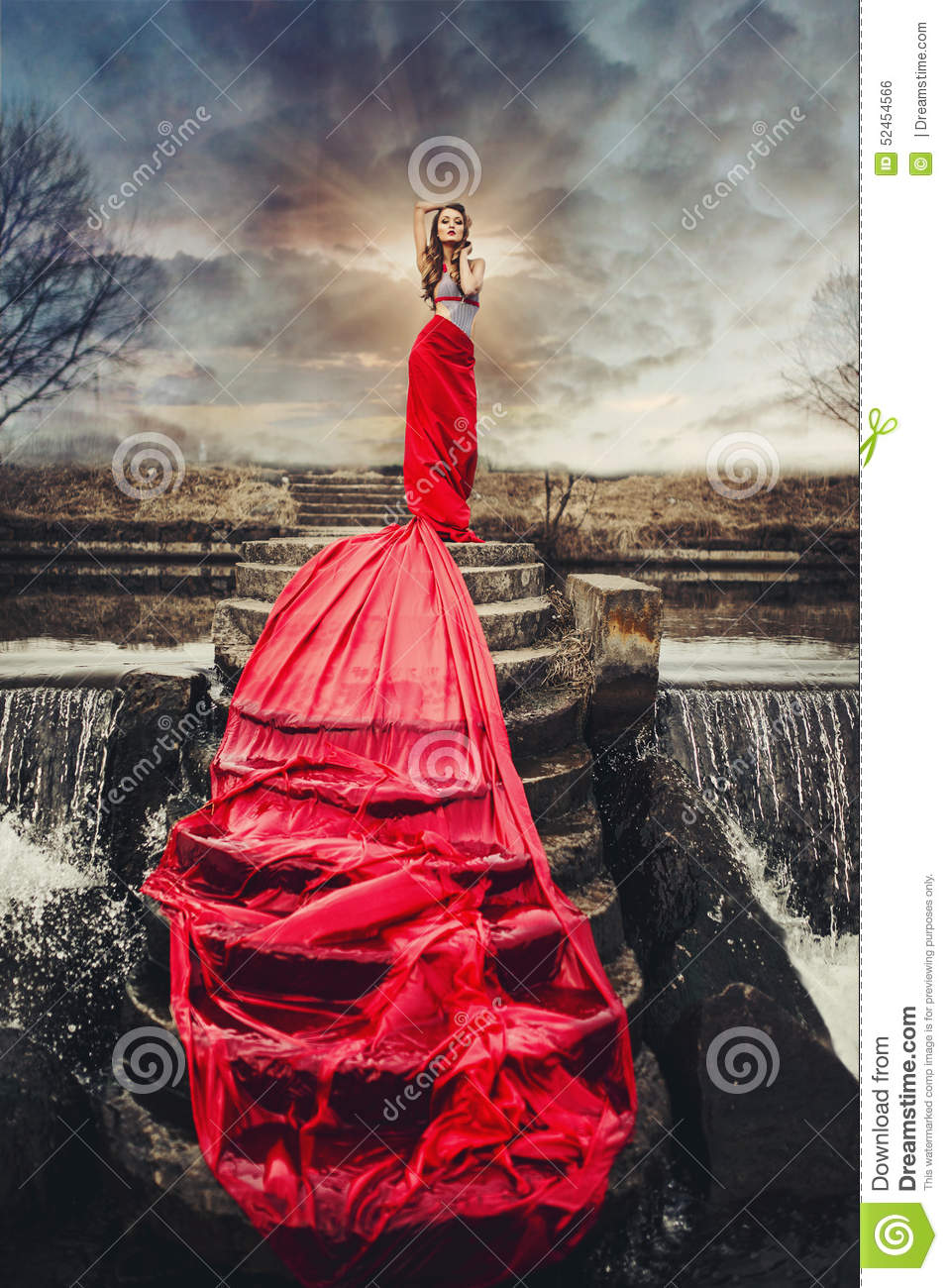 Beautiful woman in red long dress standing on a waterfall