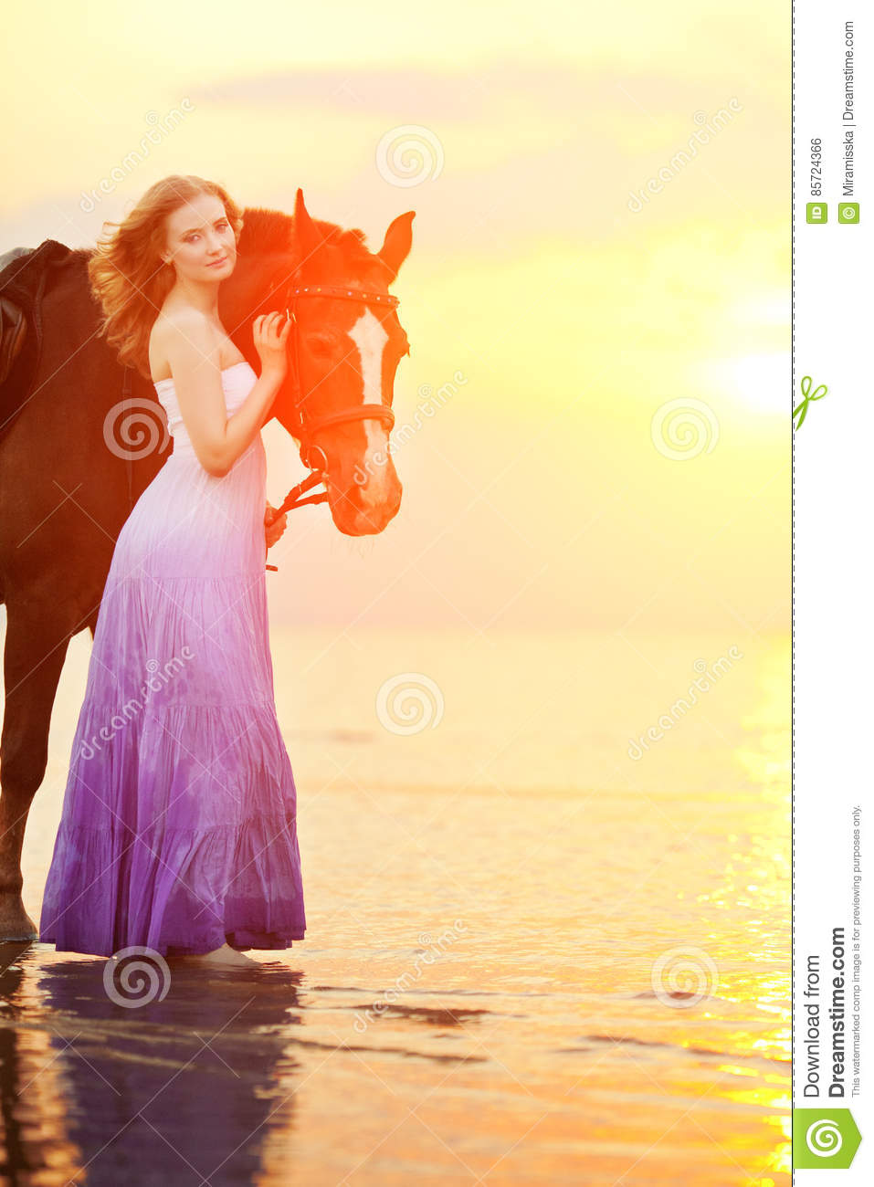 Beautiful woman riding a horse at sunset on the beach. Young girl with a horse in the rays of the sun by the sea.