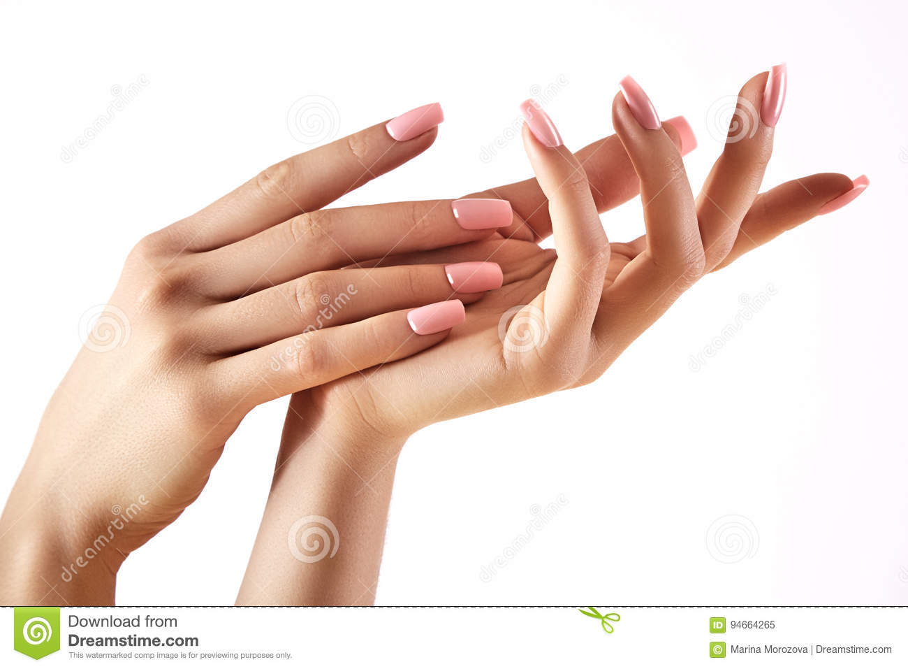 Beautiful woman`s hands on light background. Care about hand. Tender palm. Natural manicure, clean skin. Pink nails