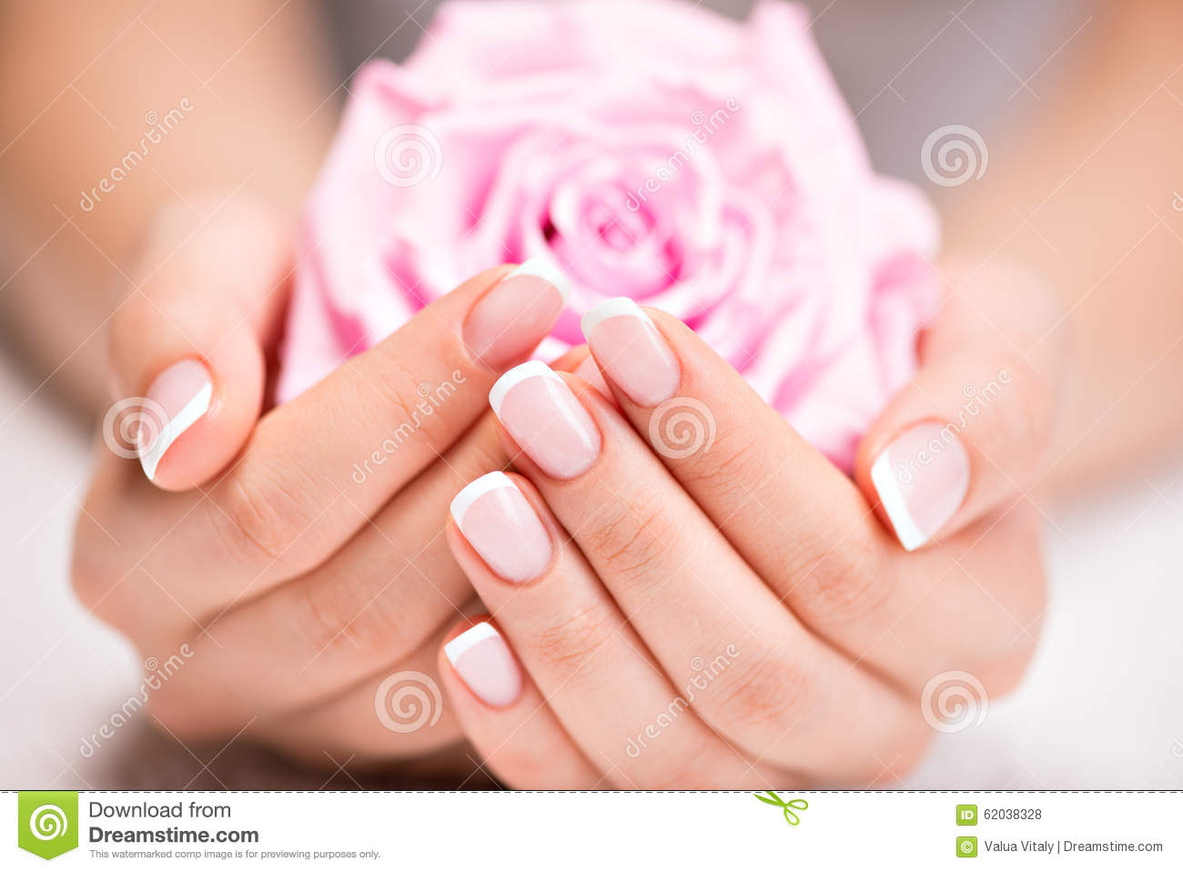 Beautiful woman s nails with french manicure and rose