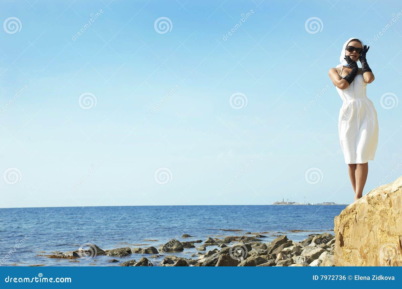 Beautiful woman on a sea beach in black gloves