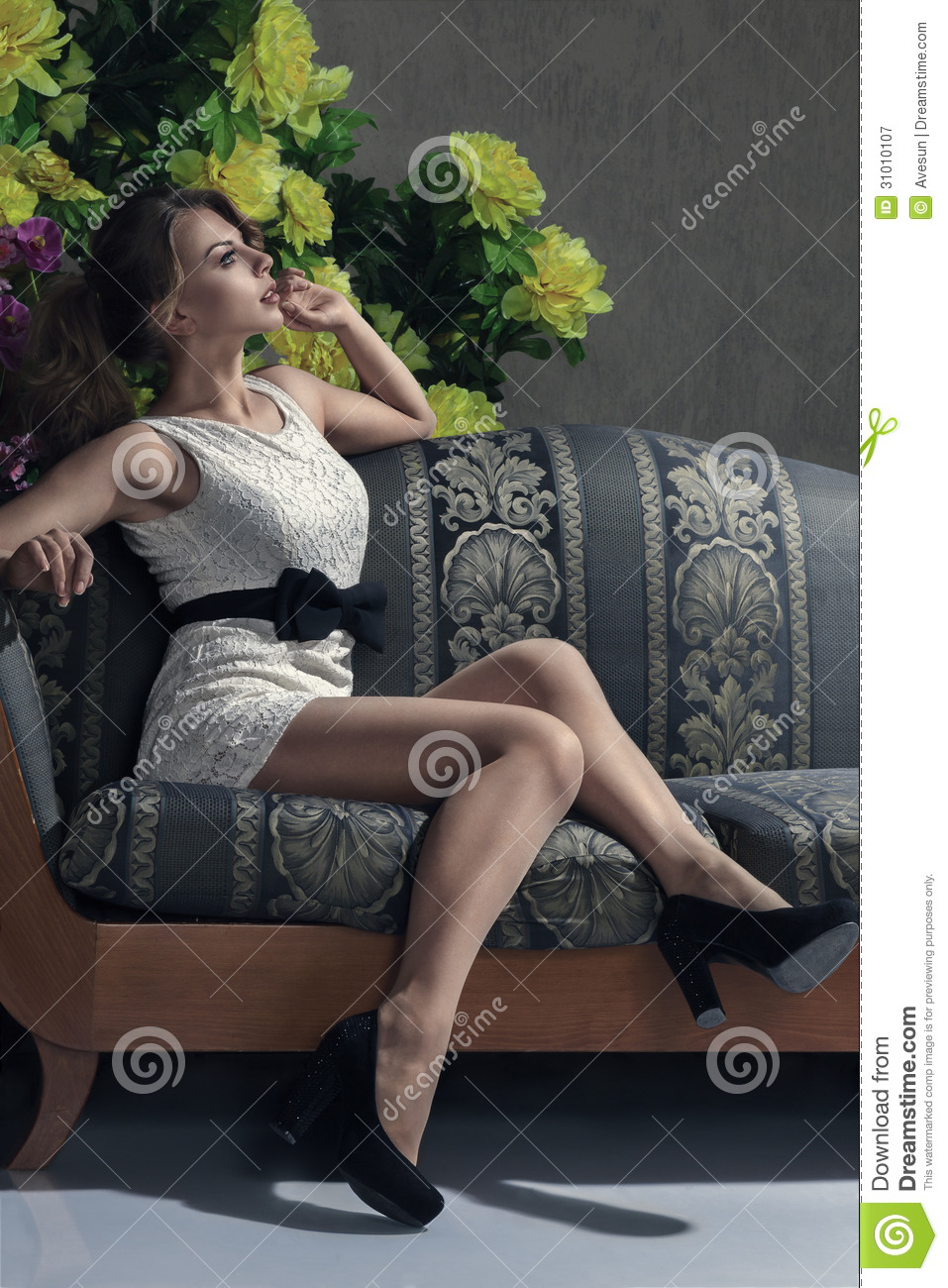 Beautiful Woman Seated On A Sofa Royalty Free Stock