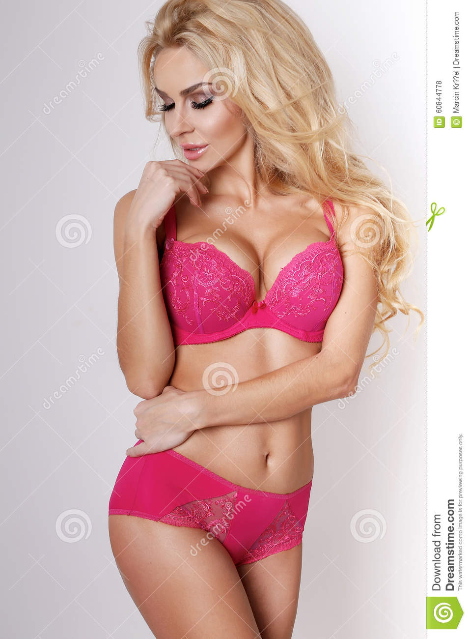 599ce8a143a7 Beautiful model woman blonde girl long hair green eyes with long slender  legs in pink erotic lingerie with lace stands on a white background
