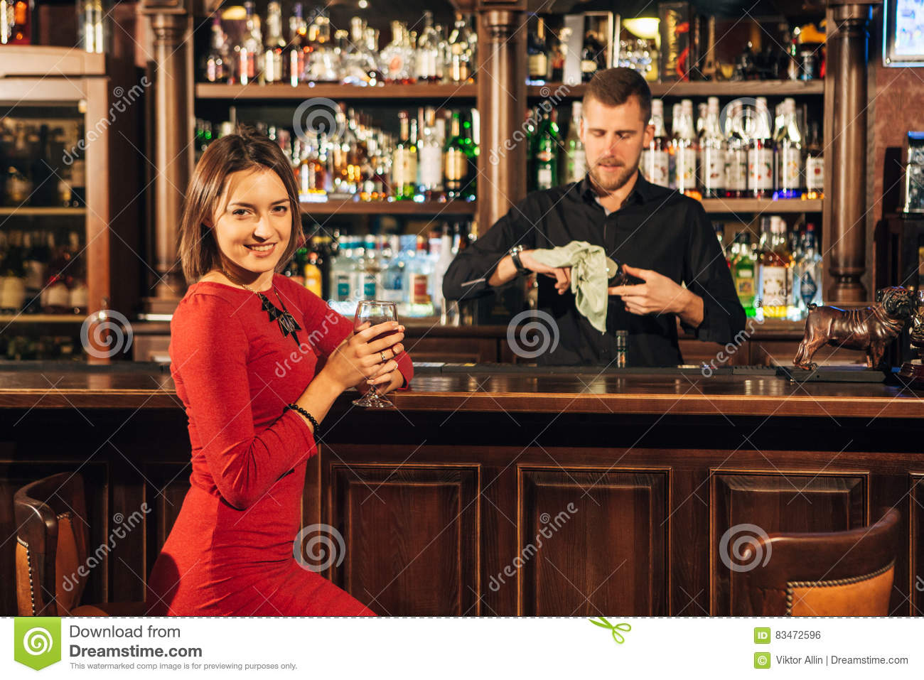 Beautiful Woman Sitting At The Bar And Waiting For Him To Mix Her