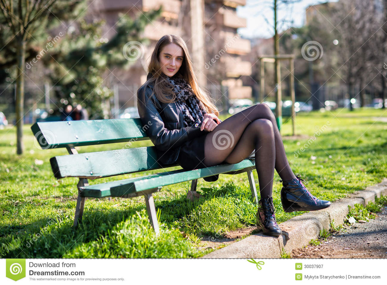 Beautiful Woman Sitting On The Bench In The Park Stock