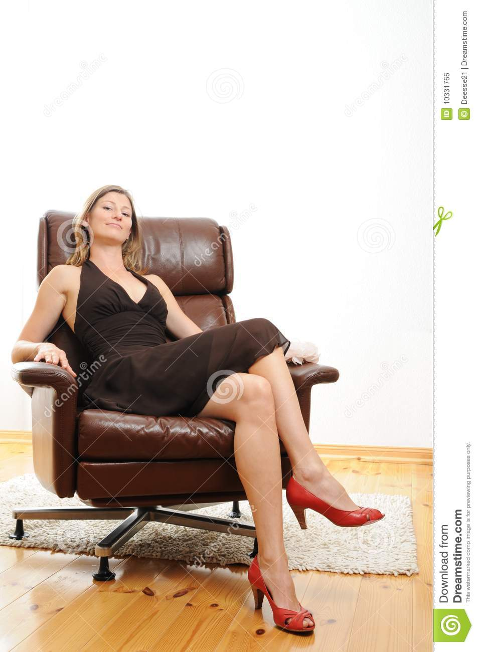 Beautiful woman sitting in an easy chair royalty free for Sitting easy chairs