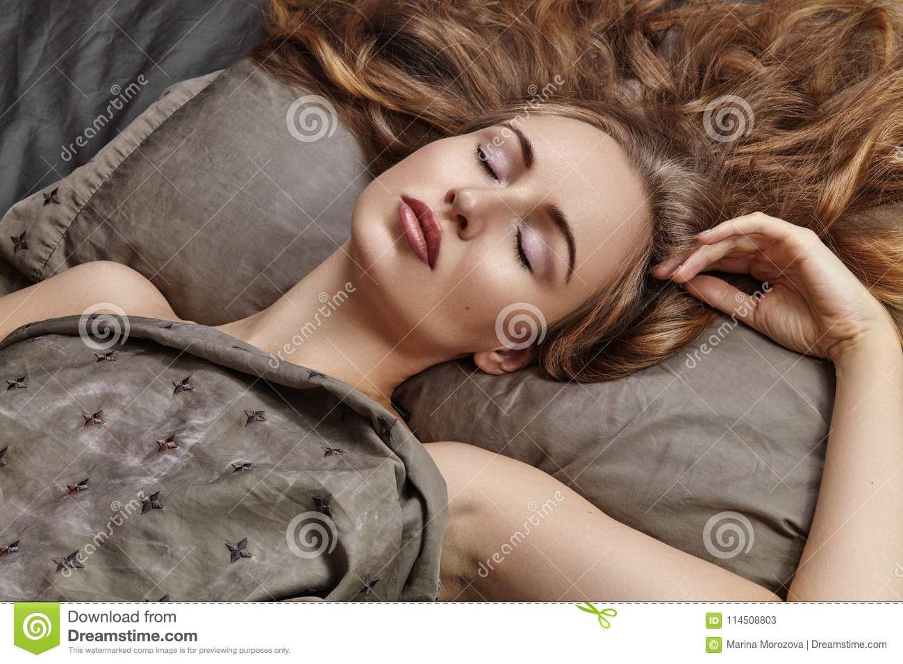 903c627427b Beautiful Woman Sleeping while lying in Bed with Comfort. Sweet dreams.  model with long curly hair relaxing on grey sheets.