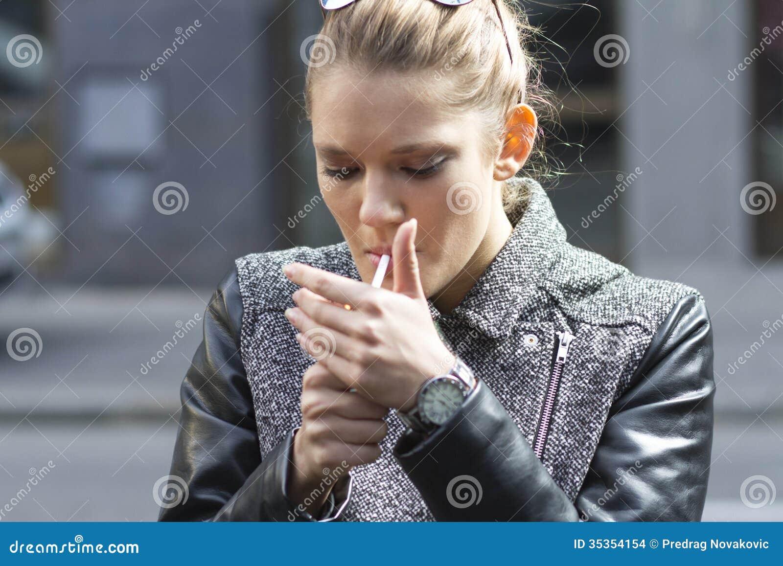 beautiful woman smokes a cigarette on the street stock