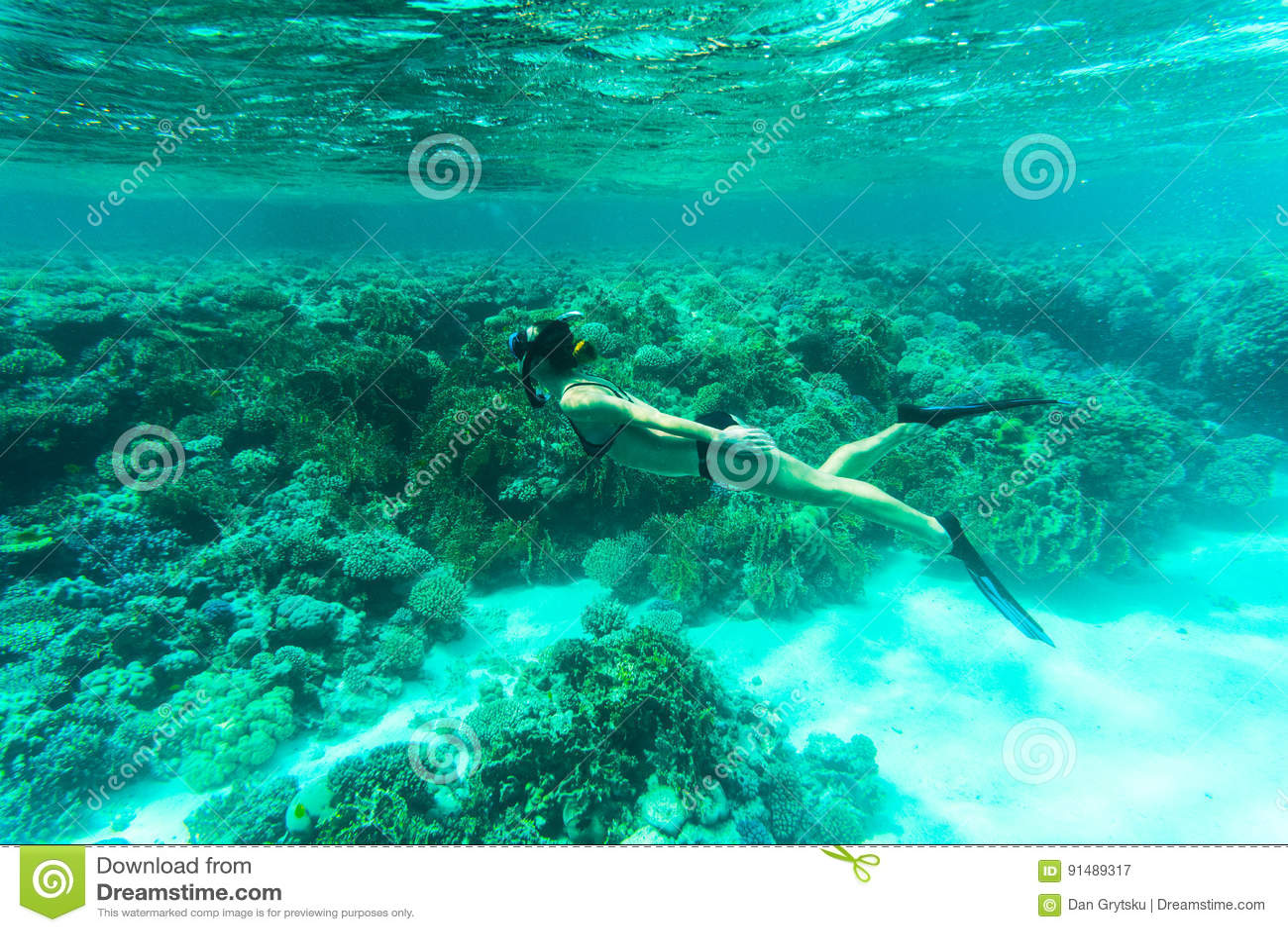 Beautiful Woman snorkeler explores coral reef in sea water